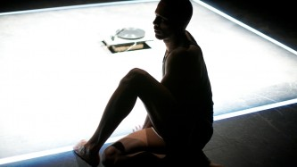 Jimmy Robert sits at the edge of a lit square on the floor, one leg bent up