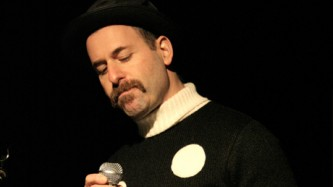 Kenny Goldsmith holds a microphone wearing a white spotted jumper