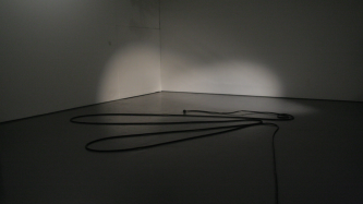 A microphone cable coiled on a grey floor