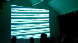 Projection of a distorted signal in blues and greens on a wall