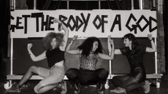 """Three women pose in front of a home made banner """"Get the Body of a God"""""""