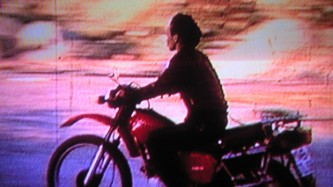 A woman rides a motorcycle against a sunset lit sky