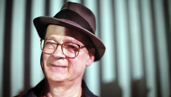 Tony Conrad smiling with glasses and a hat, a little shadow on his face