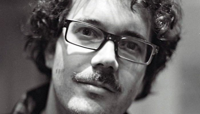 A close up portrait of Alexi Kukuljevic wearing glasses and a moustache
