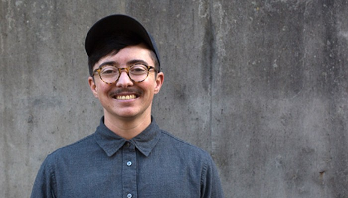 Dean Spade wearing a cap and glasses smiles broadly in front of a grey wall