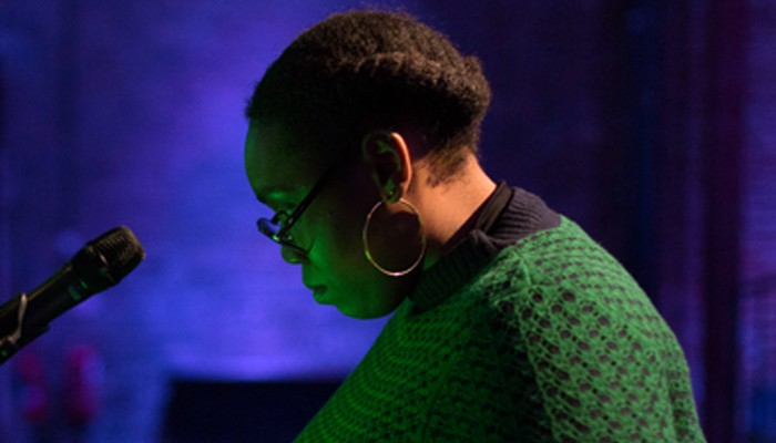 Sondra Perry's face, in profile, is lit in green, the background is blue