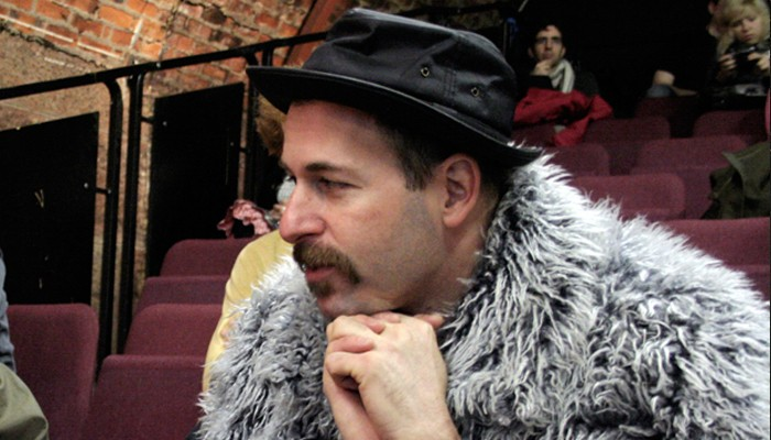Kenny Goldsmith in a porkpie hat and grey furry jacket has his chin on his hands