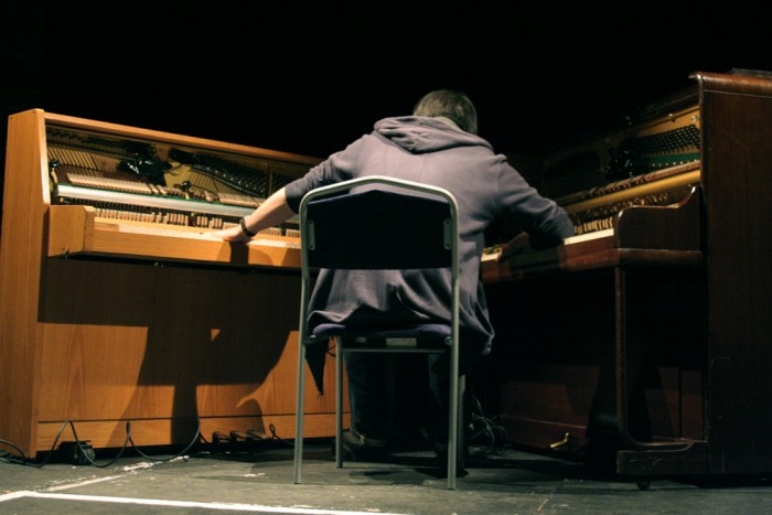Otomo Yoshihide seated between two upright pianos their interiors exposed