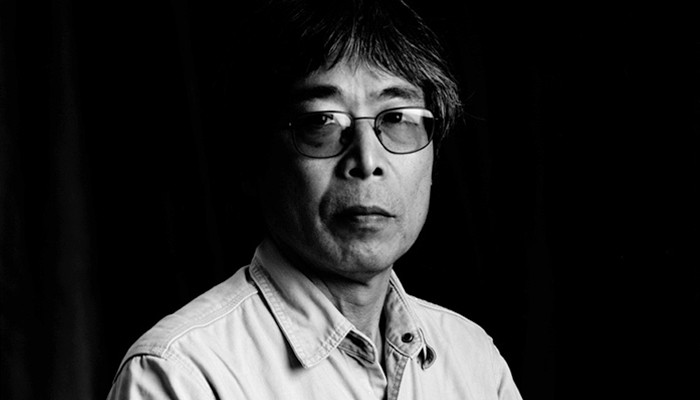Against a black backdrop Tamio in glasses and beige shirt looks at the camera