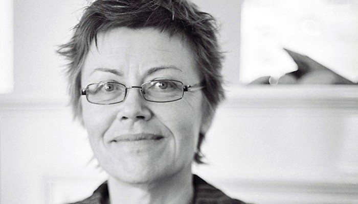 Eva Maria Houben with short hair and glasses looks into the camera