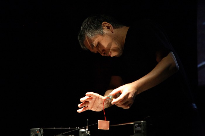 Tetsuo Kogawa peers and gently holds a contact microphone