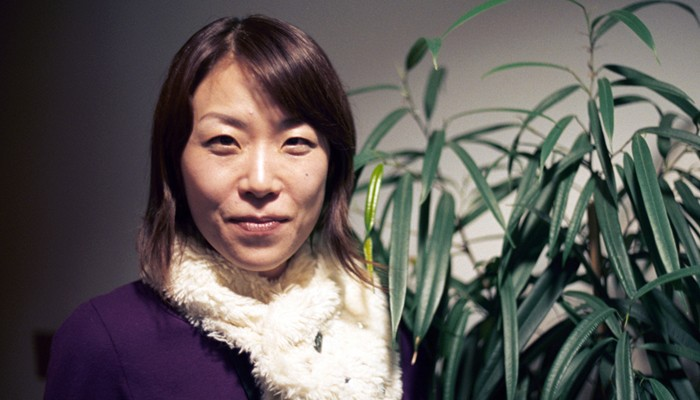 Sachiko M in cream scarf and purple top smiles at the camera next to a plant