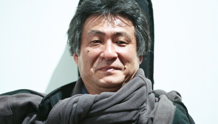Kazuo Imai wrapped in a scarf, guitar case at his back poses against a wall