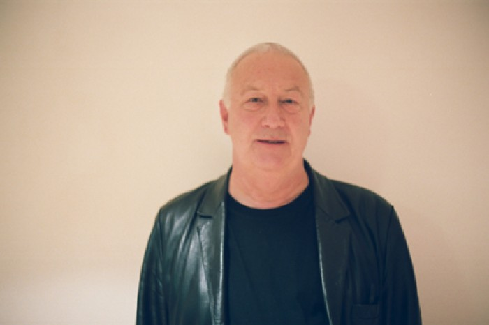 John Tilbury, in a leather jacket, stands against a neutral wall