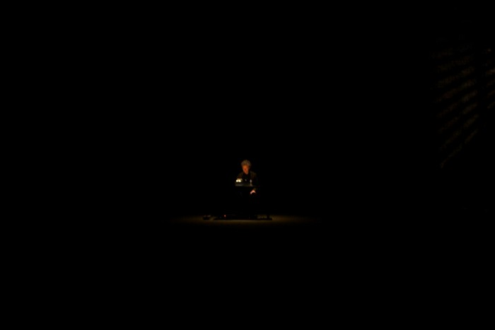 a very dark picture with a tiny dot of a person lit by a lamp in the centre