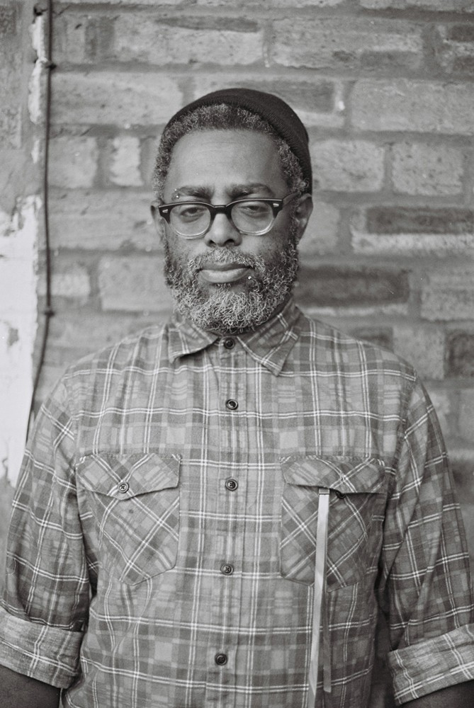 Arthur Jafa in glasses and a beanie cap looks at the camera during a portrait