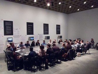 A large table seats over twenty people in a large gallery