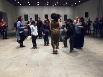 Participants move, gesture and dance on the stone floor of a large gallery