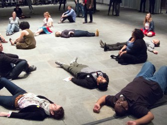Several participants have lain on the floor, others are sitting