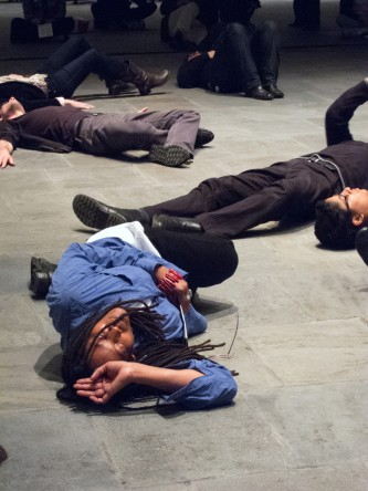 A participant with long hair and a blue shirt lies dramatically on a stone floor