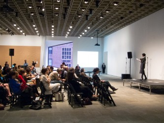 A side on shot of the audience listening to Vanessa Place in a large gallery