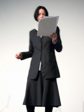 A fuzzy shot of Vanessa Place reading from papers