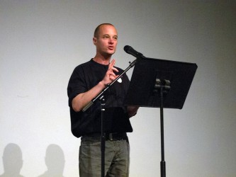 Craig Dworkin delivers a talk at a lecturn on a stage