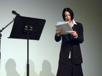 Vanessa Place reading poetry from papers, next to a lecturn