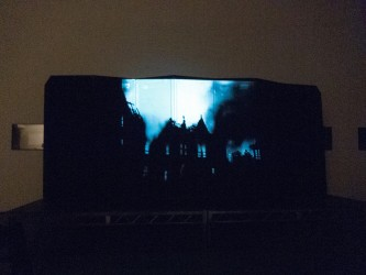 A film image of a building on fire projected onto an articulated screen