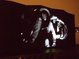A film image of a girl smiling in a hat projected onto an articulated screen