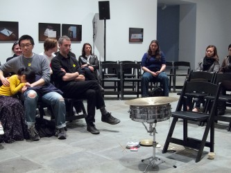 An audience sit around a now empty space, chair and drum