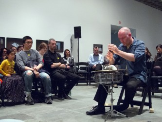 Sean Meehan in a blue shirt plays a snare drum with a wooden dowel