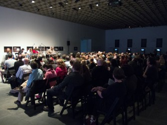 A wide shot at the back of a large seated audience in a darkened gallery space