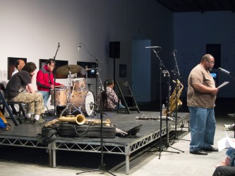 The band TEST sit on stage to the left as Fred Moten reads a poem at the right