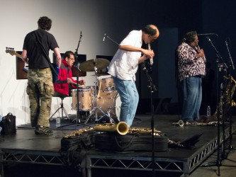 The band TEST perform on a flatly lit stage, playing bass, drums, flute and sax
