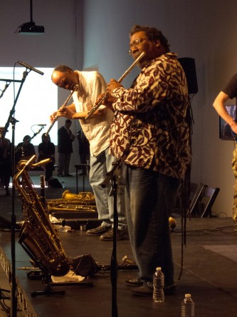 Sabir in a patterned shirt and long hair plays flute, as does Daniel behind him