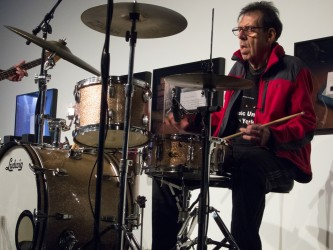 Tom Bruno in a red sweater and glasses plays drums
