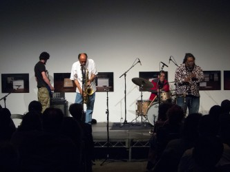 The band TEST perform on a flatly lit stage, playing bass, drums and two sax