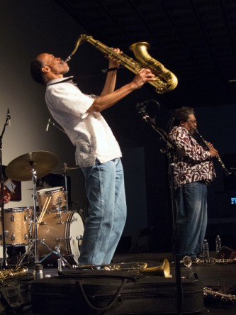 Daniel Carter leans back with closed eyes as he plays and holds a saxophone