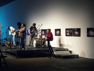 The band TEST perform on a flatly lit stage, playing bass, drums, sax & clarinet