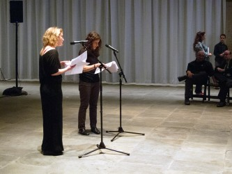 Two Participants stand and speak at microphones whilst reading from scripts