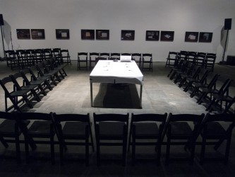 A table covered in white paper in the middle of a rectangle of chairs