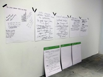 Pieces of flip chart paper with words and phrases written on them are on a wall