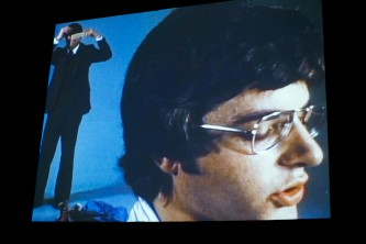 A shot of a screen showing the film Argument, a mans head reading off screen