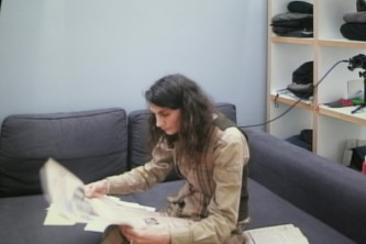 A shot of a screen showing Ayreen Anastas reading a paper on a sofa
