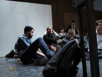 Audience members sitting on the floor during the discussion