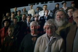 A shot of a screen showing a film by Chto Delat in which a group of people sing