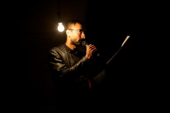 Nabil Ahmed reads by the light of a bare bulb