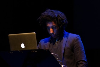 James Goodwin performs in front of a laptop in a dark room