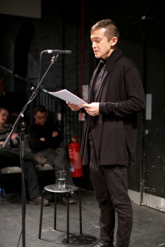 Eugene Thacker holds a paper at a microphone that they are speaking into